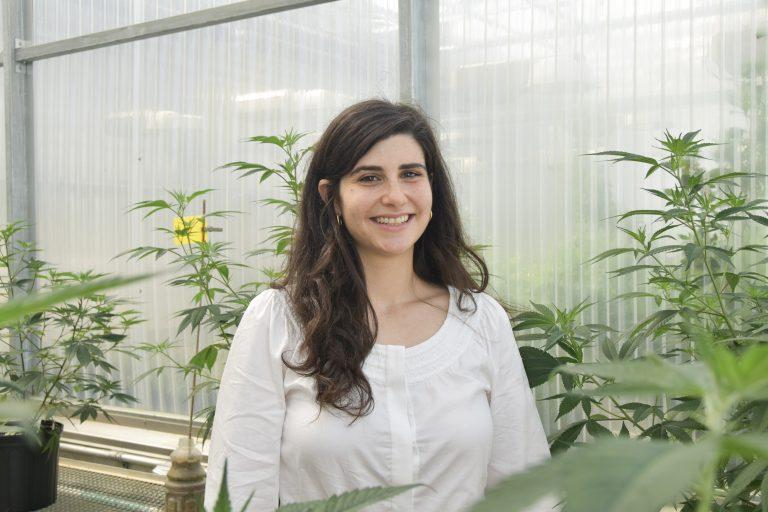 Smiling woman near cannabis plants