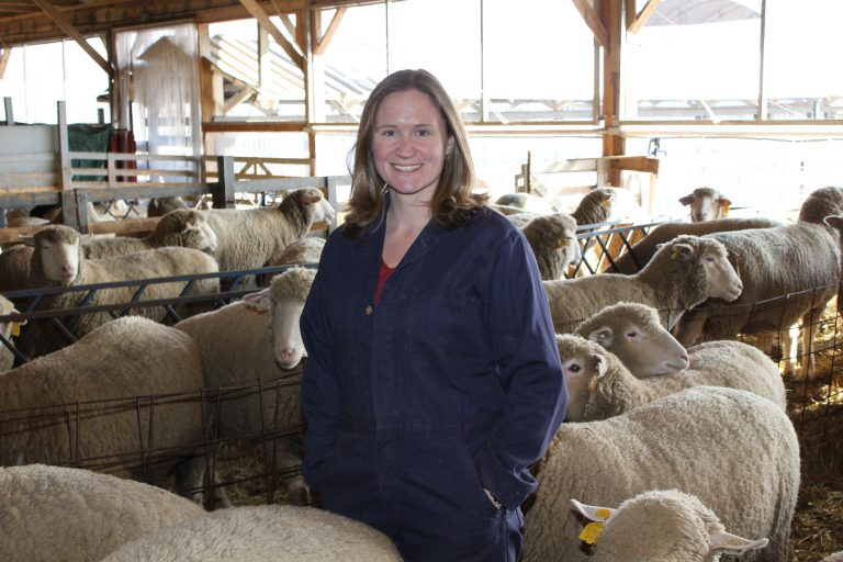 Smiling woman near sheep